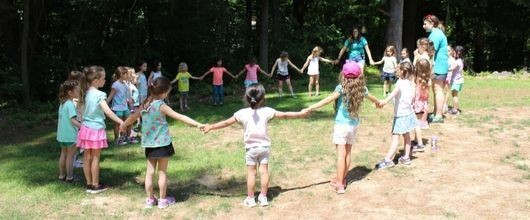 Girl Scouts holding hands in a circle outdoors