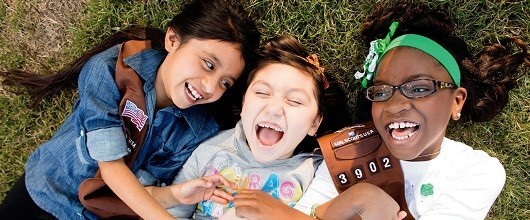 Three Girl Scout Brownies smiling outdoors