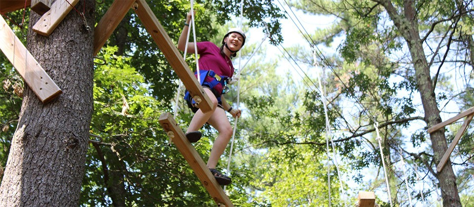 A Girl Scout on a high ropes course at camp
