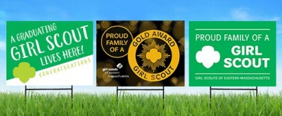 Three lawn signs on green grass: A Graduating Girl Scout Lives here! Congratulations; Proud Family of a Gold Award Girl Scout; Proud Family of a Girl Scout
