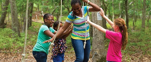 A Girl Scout volunteer with three Girl Scouts on a low ropes course