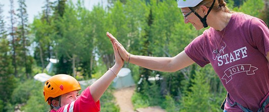 A Girl Scout camp staff member high-fiving a Girl Scout outdoors